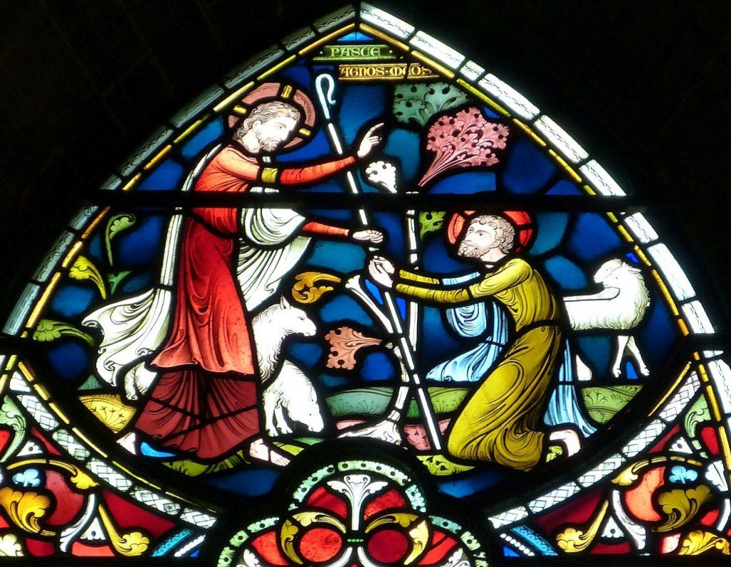 Der Psalm vom Guten Hirten: Kirchenfenster mit Jesus, umgeben von Schafen und mit einem Hirtenstab in der Hand, der einen vor ihm knienden Mann segnet