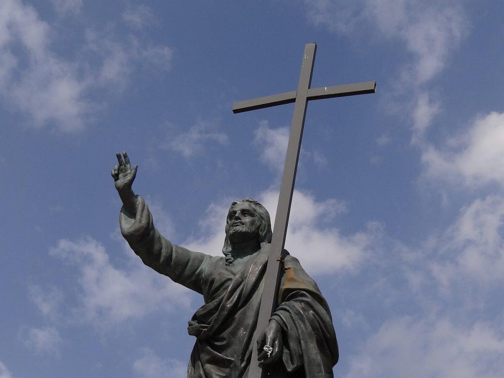 Wer an Jesus glaubt, muss keine Angst haben: Jesus trägt das Kreuz, macht mit der rechten Hand das Siegeszeichen bzw. eine segnende Geste - vor einem blauen Himmel mit weißen Wölkchen