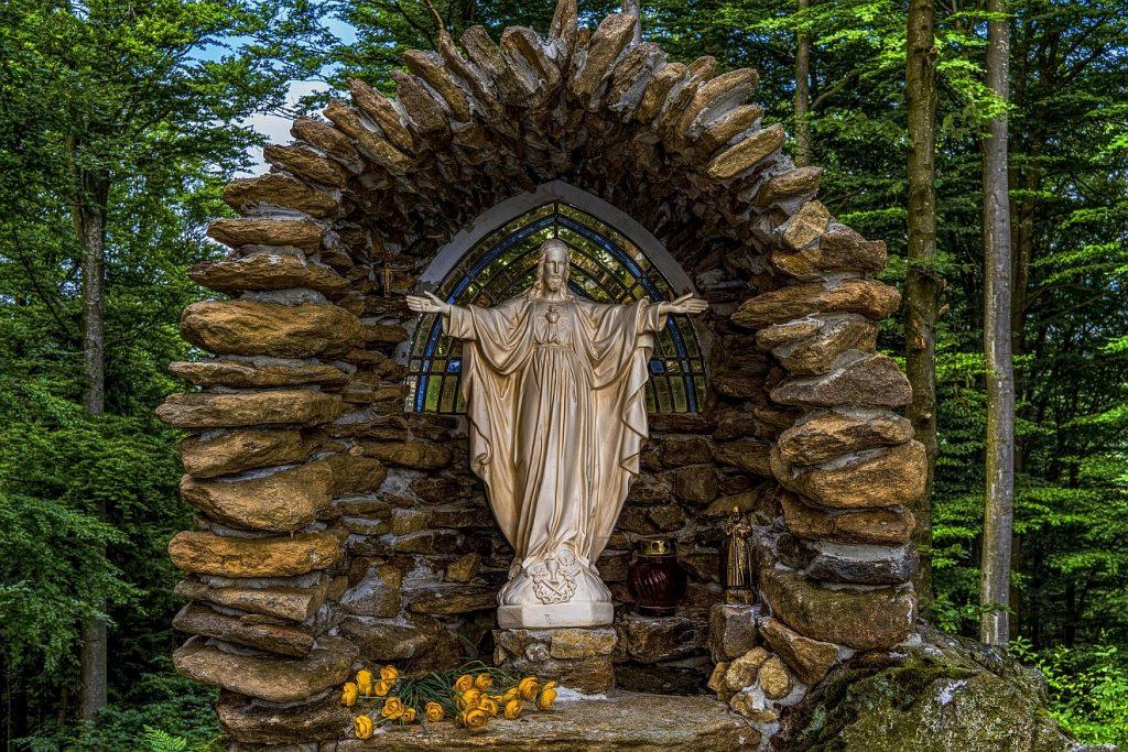 Im Vertrauen auf Jesus leben und sterben: Eine Kapelle im Wald, Jesus steht in einem gotischen Bogen mit ausgebreiteten Armen
