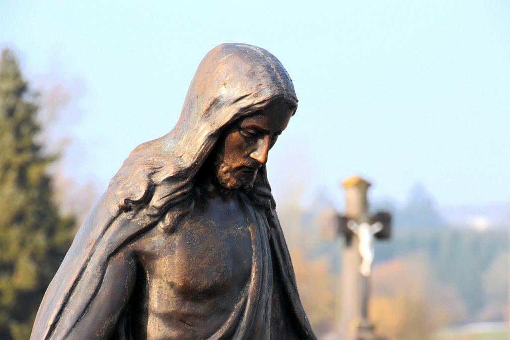 Seliges Sterben: Eine Jesus-Statue, die nach unten blickt; im Hintergrund ein Kruzifix auf einem Friedhof