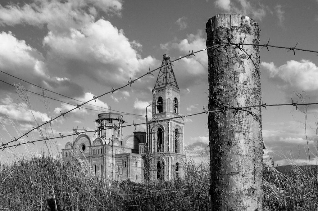 Zwischen Deportation und Bewahrung: Eine verfallen wirkende Kirche in Sibirien, im Vordergrund ein dicker Zaunpfahl mit Stacheldraht