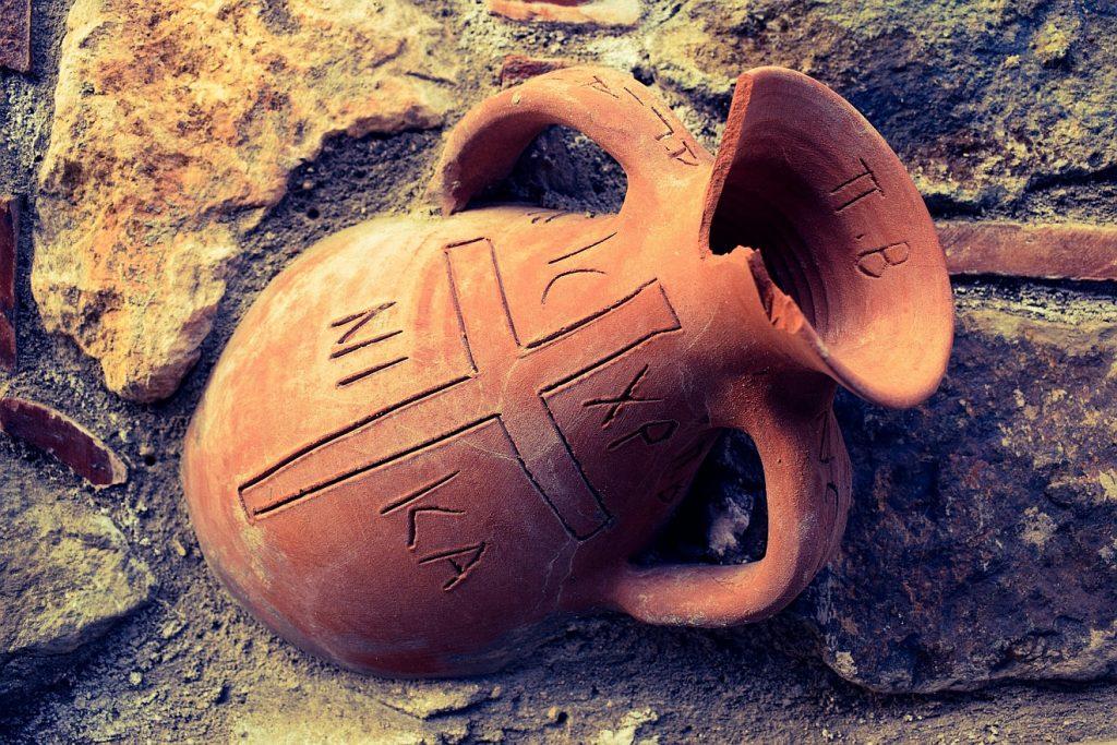 """Ein etwas beschädigter antiker Krug mit der Aufschrift """"IS CHR NI KA"""" um ein Kreuz herum = """"Jesus Christus siegt!"""""""