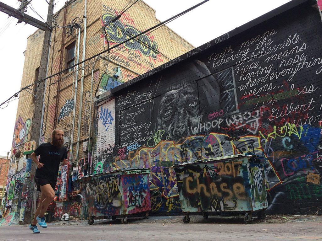 """Jagd nach Gerechtigkeit: Ein Jogger läuft an Wänden und Mülltonnen entlang, die mit einer Unzahl von Graffiti verziert sind; auf einer Mülltonne steht """"Chase"""" = """"Jagd"""""""