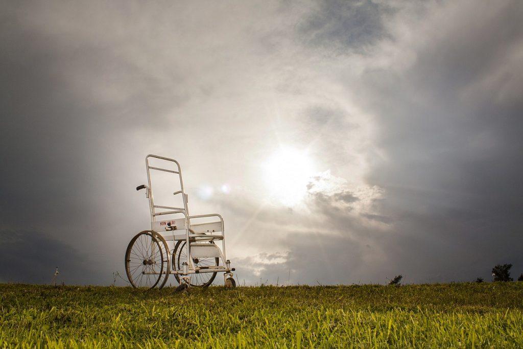 Wie hilft uns Gott? Ein leerer Rollstuhl steht auf einer Wiese unter einem bewölkten Himmel, durch den man die Sonne erkennen kann