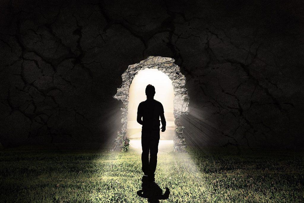 """""""Seid fröhlich in Hoffnung!"""" Ein Mann geht auf eine Tür in einer dunklen Mauer zu, durch die strahlend helles Licht hereinfällt"""