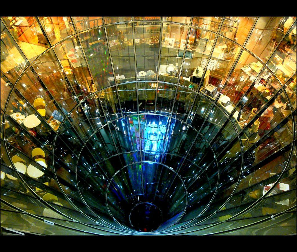 Licht für die Abgründe der Welt: Eine runde Glaswand umschließt einen dunklen Abgrund, hinter der Wand scheint Kaufhauslicht zu leuchten