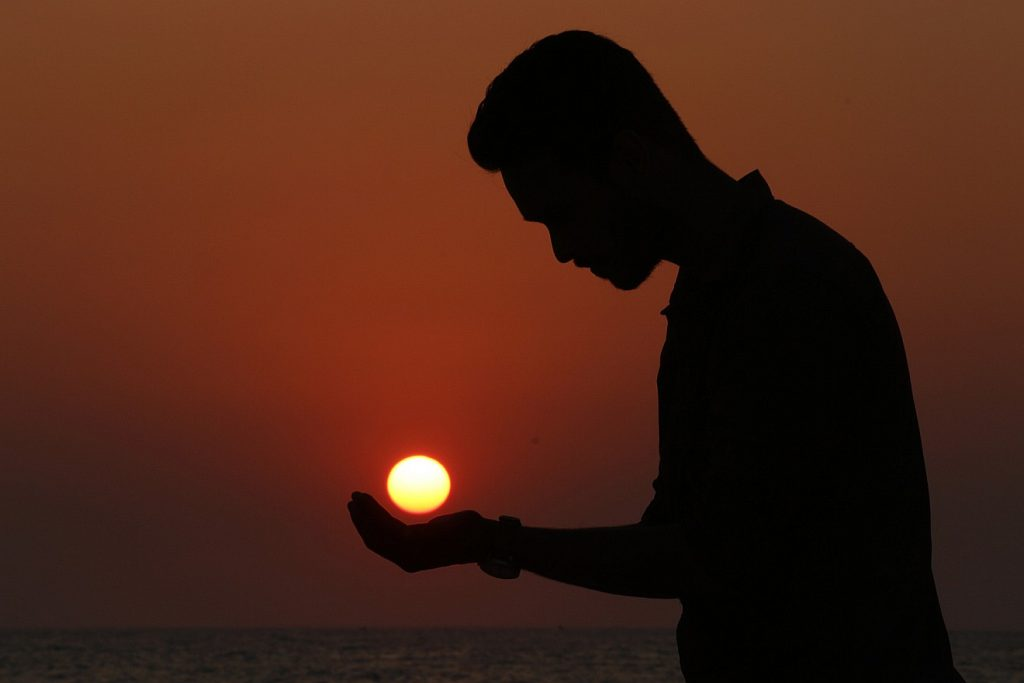 Der Schatten eines Mannes vor dem Meer, er hält die Hand unter die untergehende Sonne