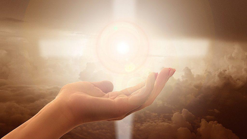 Ein Kreuz aus Licht über einer nach oben geöffneten Hand