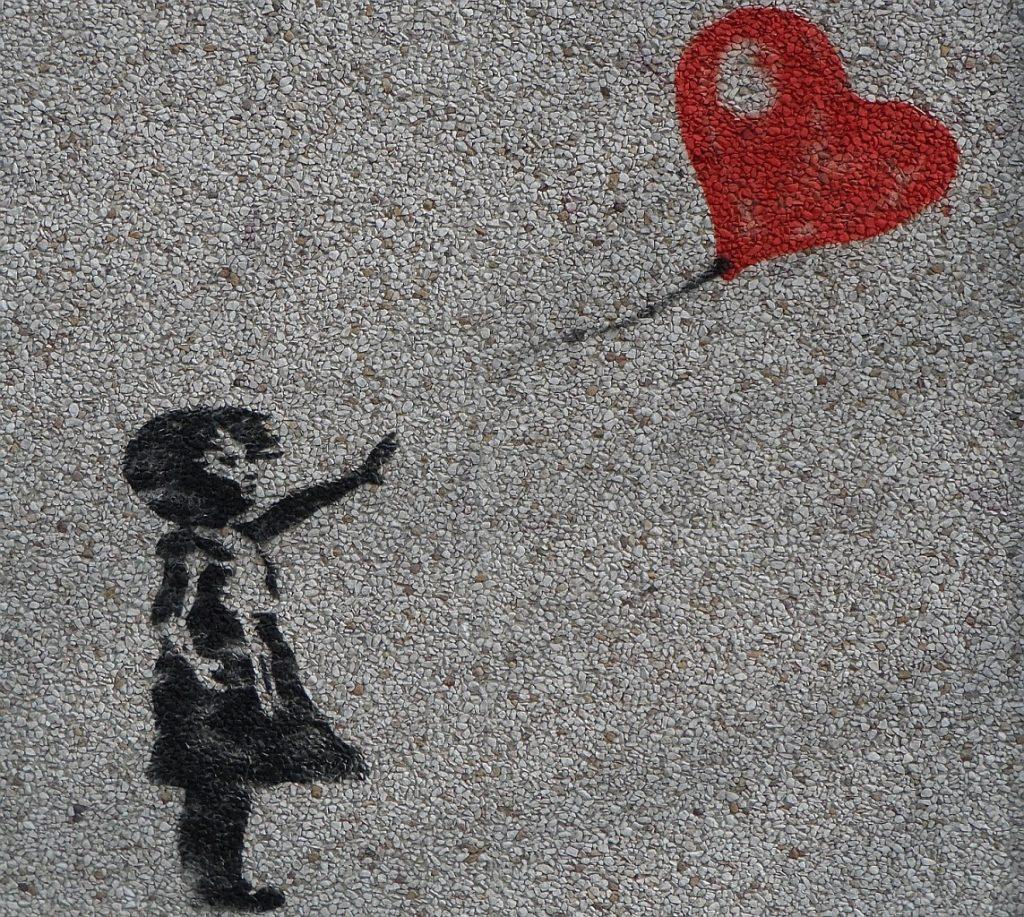 Ein Koma-Patient darf endlich sterben: Bild eines Mädchens, das einen herzförmigen Luftballon loslässt, an einer Hauswand