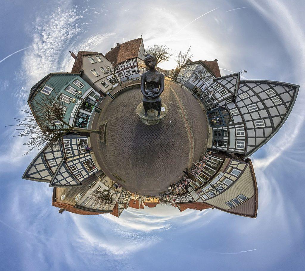 Weiter Raum in einer festen Stadt: Einen Marktplatz mit der Statue einer Marktfrau in der Mitte umgibt wie einen kleinen Planeten eine Häuserzeile und ein blauer Himmel