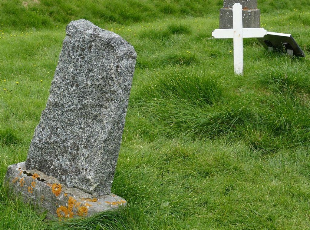 Beerdigung im Niemandsland: Ausschnitt eines Bildes aus Island mit schiefen Grabsteinen und einem weißen Kreuz ohne Namen auf einer Wiesenlandschaft