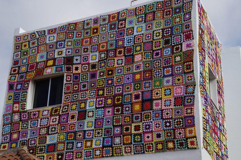 Überfließende Liebe in einer Patchworkfamilie: Ein Haus, beklebt mit einer Wanddekoration aus Patchworkdecken