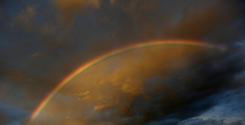 Der Weg über die Regenbogenbrücke: Ein Regenbogen zieht sich über einen oben dunklen, unten helleren Abendhimmel