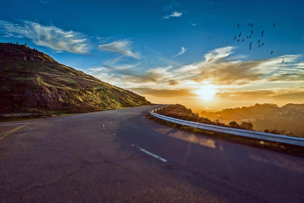 Reise in den Himmel: Eine Straße führt an Bergen entlang in die Weite, hinten ist ein schöner Abendhimmel mit einem Vogelschwarm zu sehen