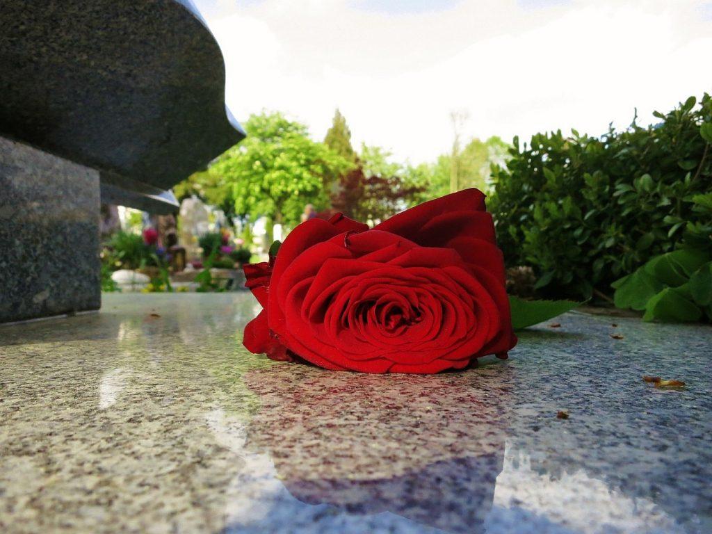 """""""Deine Güte ist besser als Leben"""": Eine Rose liegt auf der Marmorplatte, die ein Grab abdeckt"""