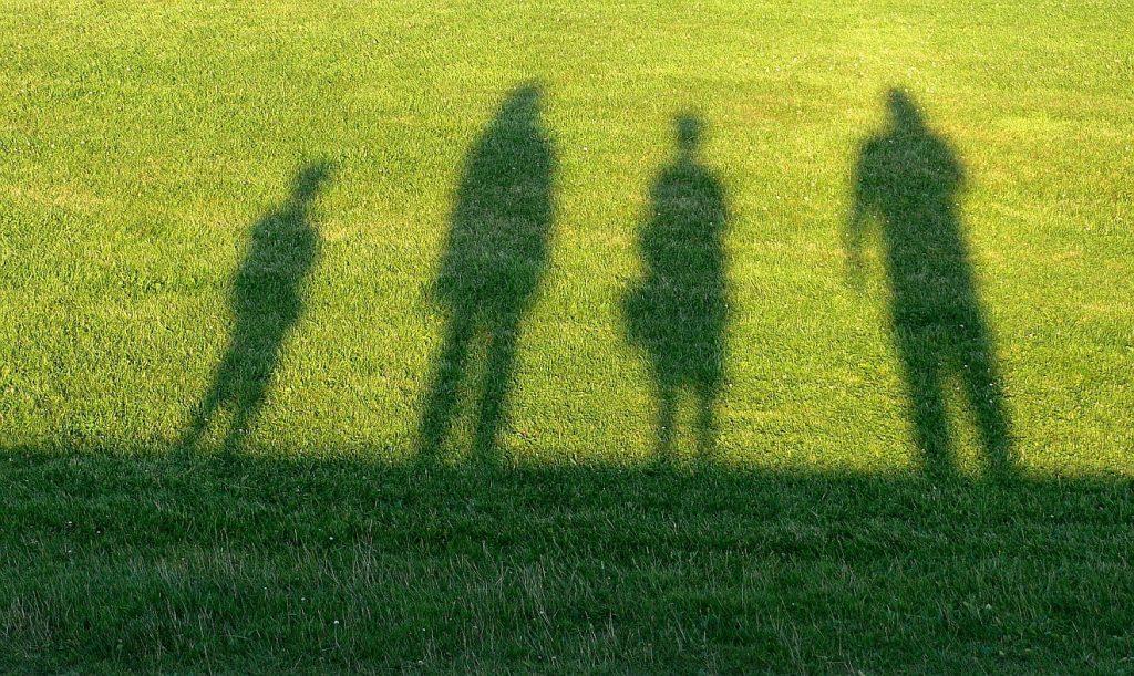 Verlassen - und dennoch aufgenommen: Schatten von Vater, Mutter und zwei Kindern auf einer Wiese