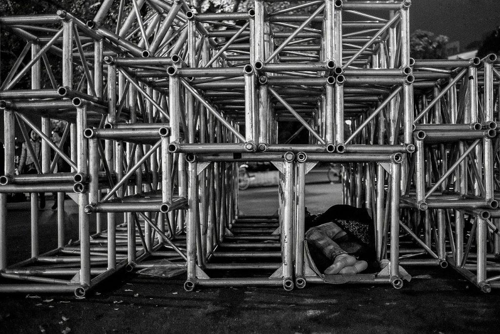 Nachträgliche Trauerfeier für einen Obdachlosen: Ein Obdachloser schläft in einem riesigen Gestell aus Rohren unter freiem Himmel