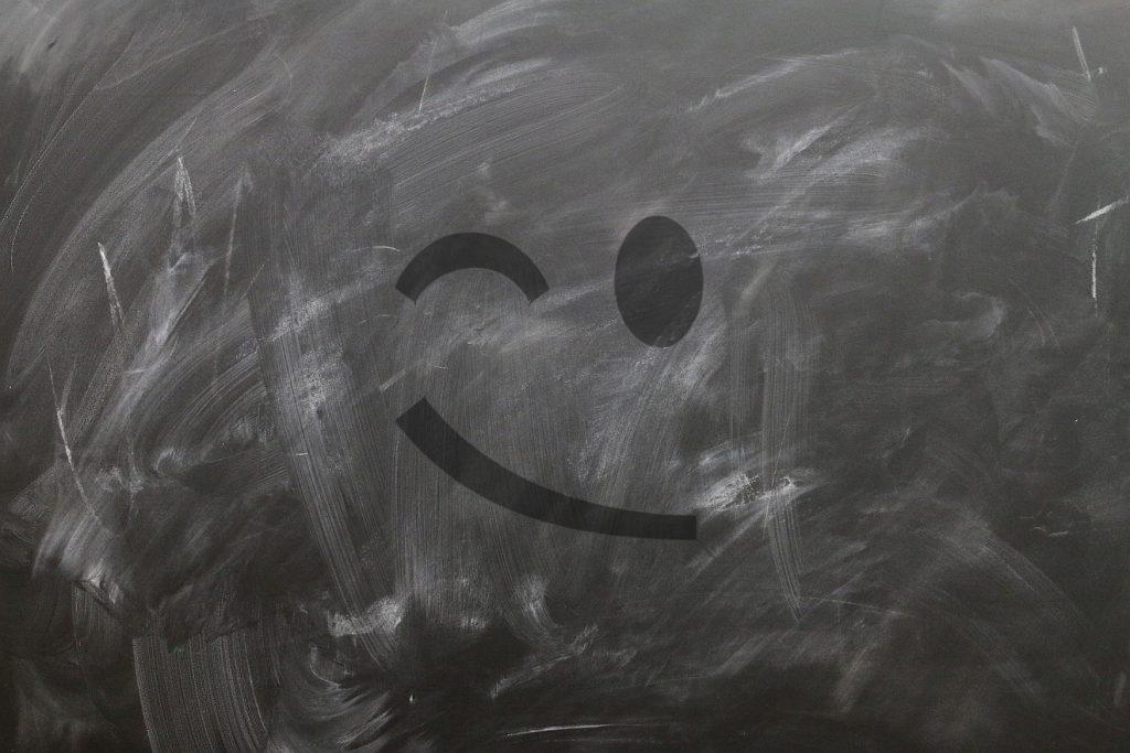 Schule für unsere Gefühle: Eine schlecht abgewischte Schultafel mit einem Zwinkersmilie