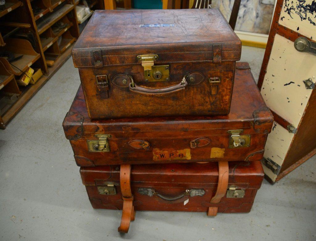 Schweres Gepäck hinter sich lassen: Drei schwere alte Koffer, aufeinander gestapelt