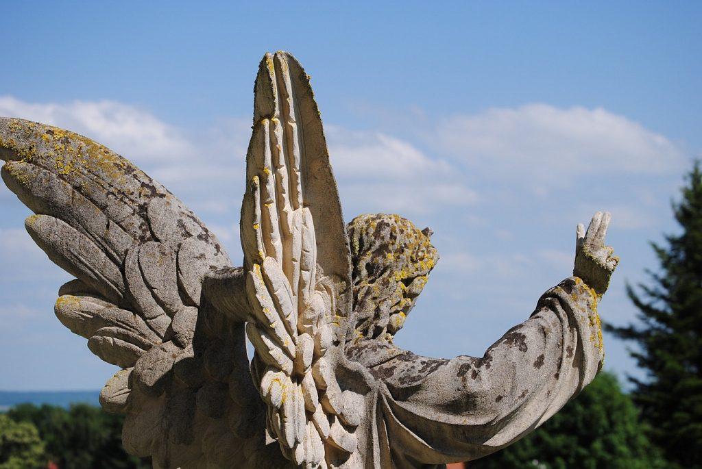 Stärkende Engel: Eine Engel-Skulptur auf einem Friedhof mit segnend erhobenem Arm von hinten gesehen