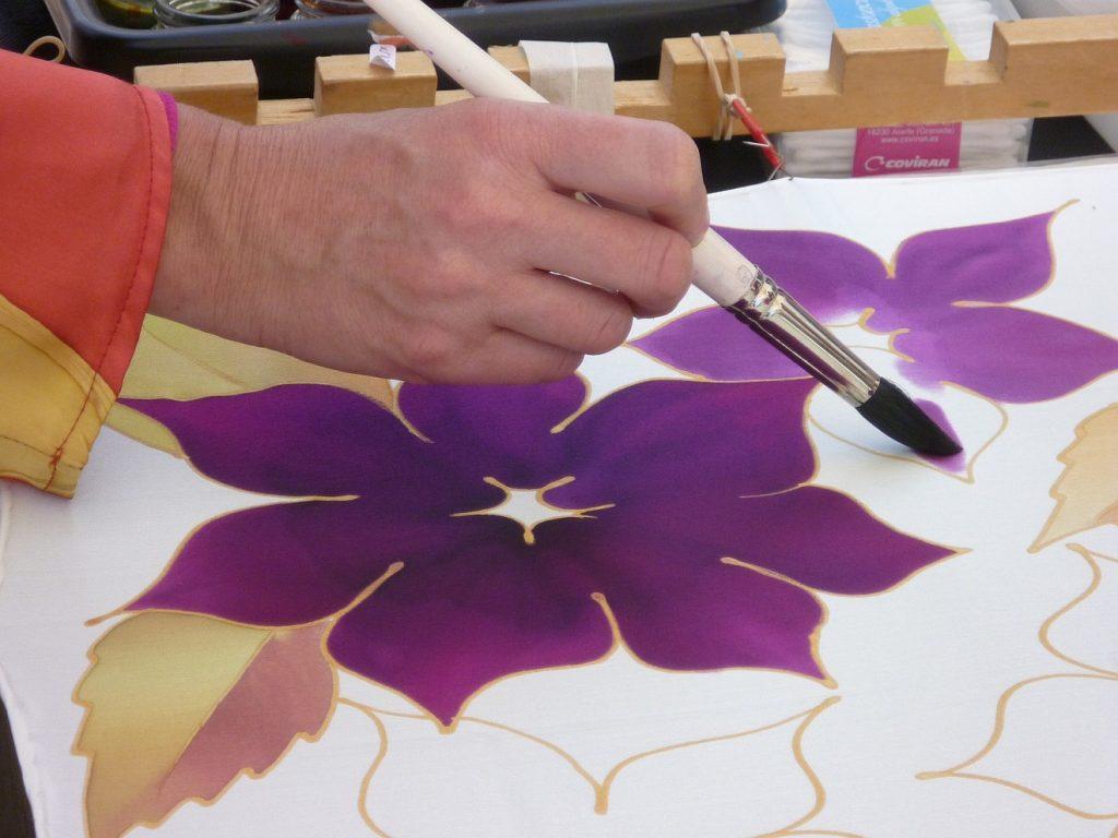 Mitten durchs Leiden hindurch geführt: Eine Hand führt einen Pinsel, die Blumen auf Seide ausmalt