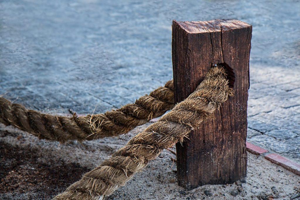 """""""Zukunft hat der Mann des Friedens"""": Ein Seil ist durch ein Loch in einem starken Pfahl hindurchgeführt, um feste Verbindungen herzustellen"""