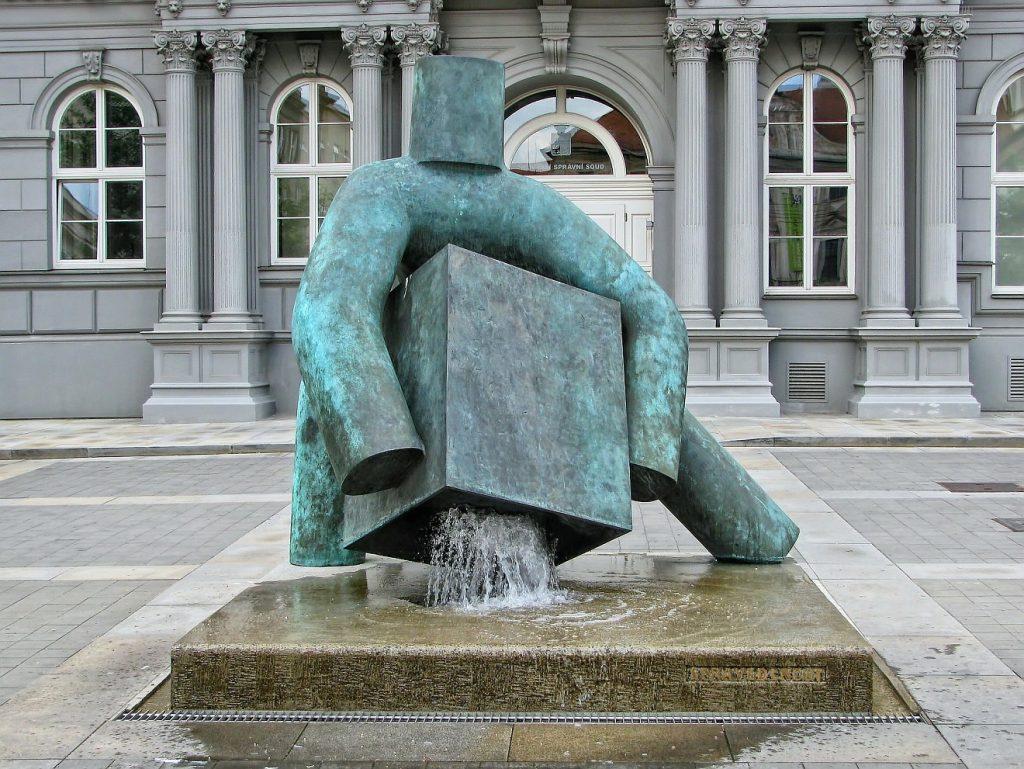 Hunger und Durst nach Gerechtigkeit: Die Skulptur eines stilisierten starken Mannes, der einen Würfel anhebt, unter dem Wasser aus einem Brunnen hervorsprudelt