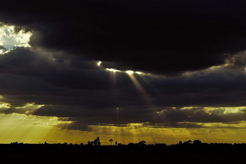 Sonnenstrahlen brechen durch schwarze Wolken hindurch