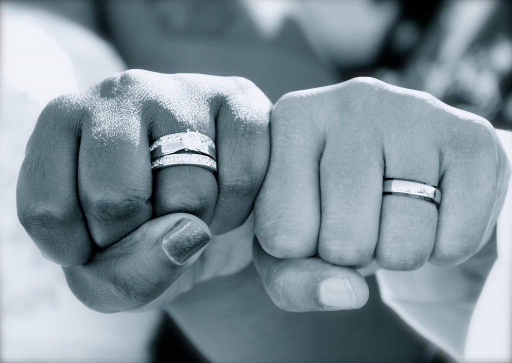 Inneres Standhalten: Zwei Fäuste mit Eheringen nebeneinander halten allem stand