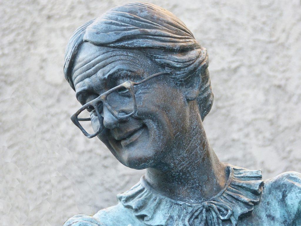 Eine Frau, die in sich ruht: Statue einer älteren Frau mit Brille und Stirnfalten, die mit scharfen Augen schaut und lächelt