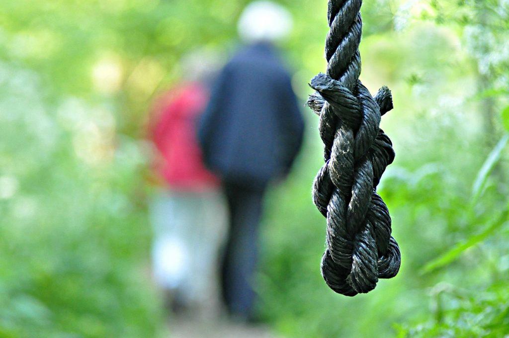 Zorn und Schuld, Machtlosigkeit und Verzweiflung: Ein dunkler Strick hängt ins Bild, dahinter verschwommen zwei Personen von hinten, die durch einen grünen Garten gehen