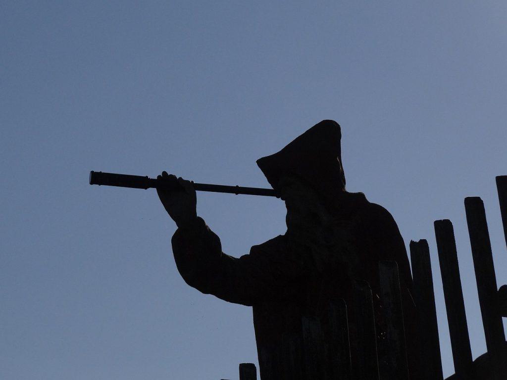 """""""Suchet den HERRN, so werdet ihr leben!"""" Silhouette eines Mannes mit Kapze, der mit einem Fernrohr in die Ferne schaut, vor blauem Himmel"""