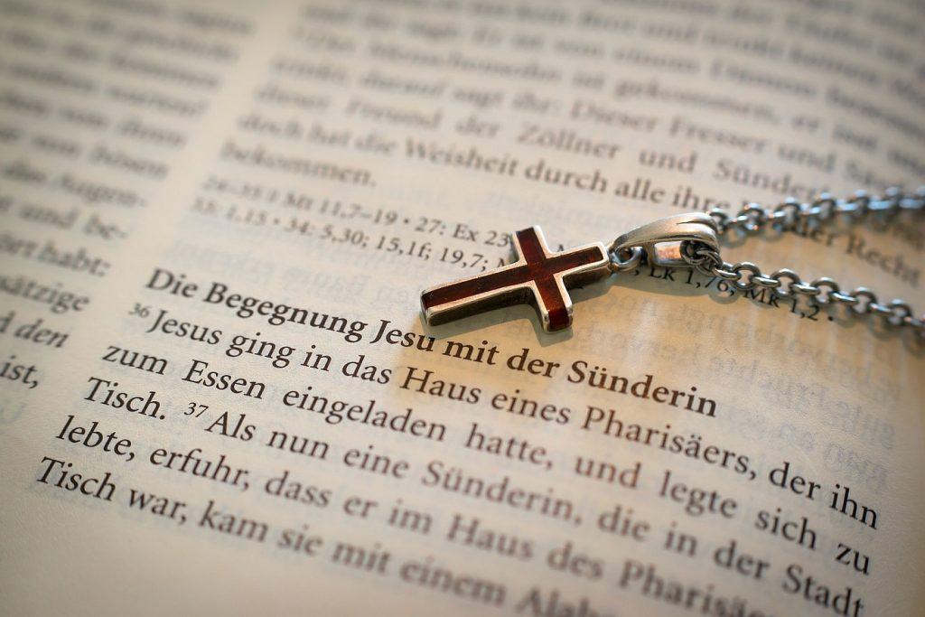 Versöhnung und Heilung: Ein Kreuz an einer Halskette liegt auf der Bibel, wo von der Begegnung Jesu mit der Sünderin erzählt wird