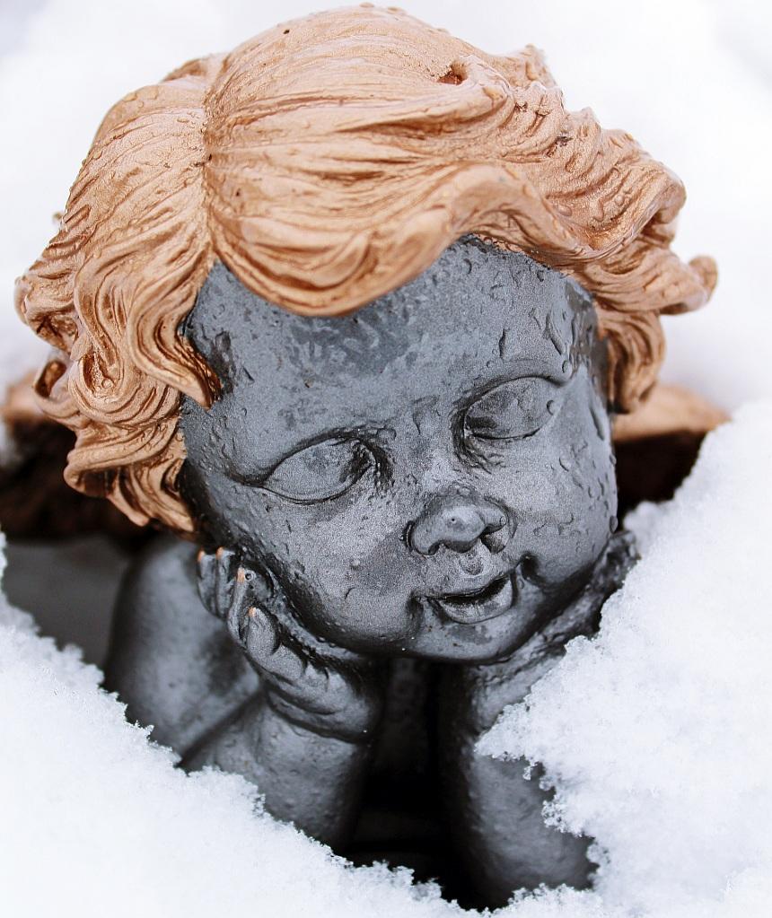 Trauerfeier für ein glückliches Kind: Ein kindlicher Engel aus Stein mit bräunlichen Haaren, von Schnee umgeben, das Gesicht mit geschlossenen Augen in die Hände gestützt.