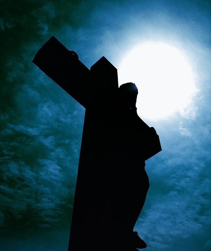 Trost in der Todesnacht: Ein Kruzifix als Schatten vor einem Licht, das in der Dunkelheit scheint