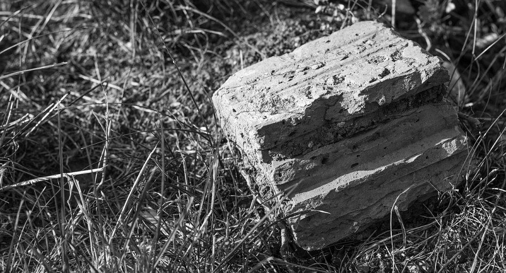Jesus, der Eckstein: ein weggeworfener Stein liegt im Dreck