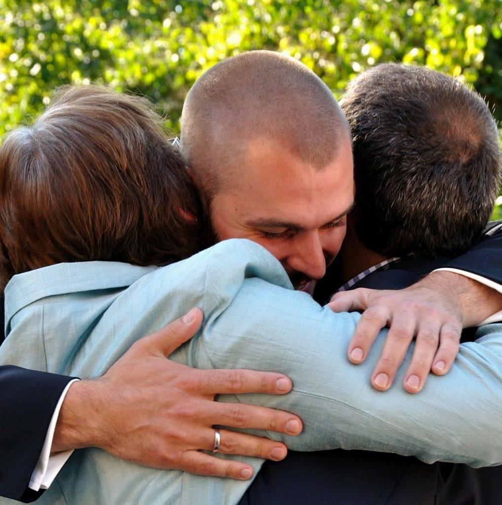 Wiedersehen macht Freude: Das Bild zeigt drei Menschen, die sich in Wiedersehensfreude umarmen