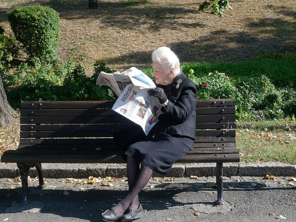 Eine alte Frau, die Zeitung lesend auf einer Parkbank sitzt