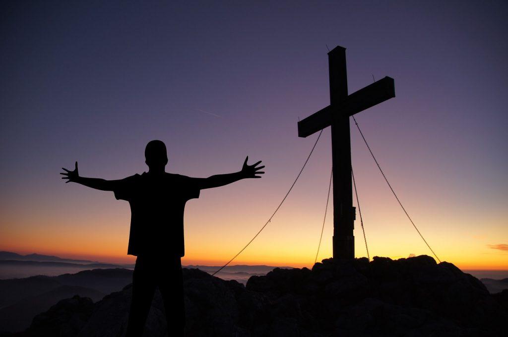 Schattenriss eines Kreuzes vor Sonnenauf- oder -untergang und ein Mensch mit ausgebreiteten Armen