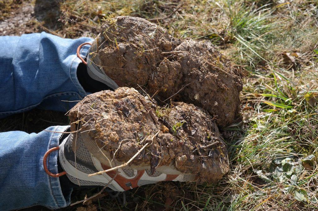 Jemand liegt auf der Erde, man sieht nur die Schuhe, auf deren Unterseite Gartenerde klebt
