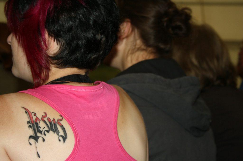 """Der Name """"Jesus"""" als Tattoo auf dem Rücken einer jungen Frau"""