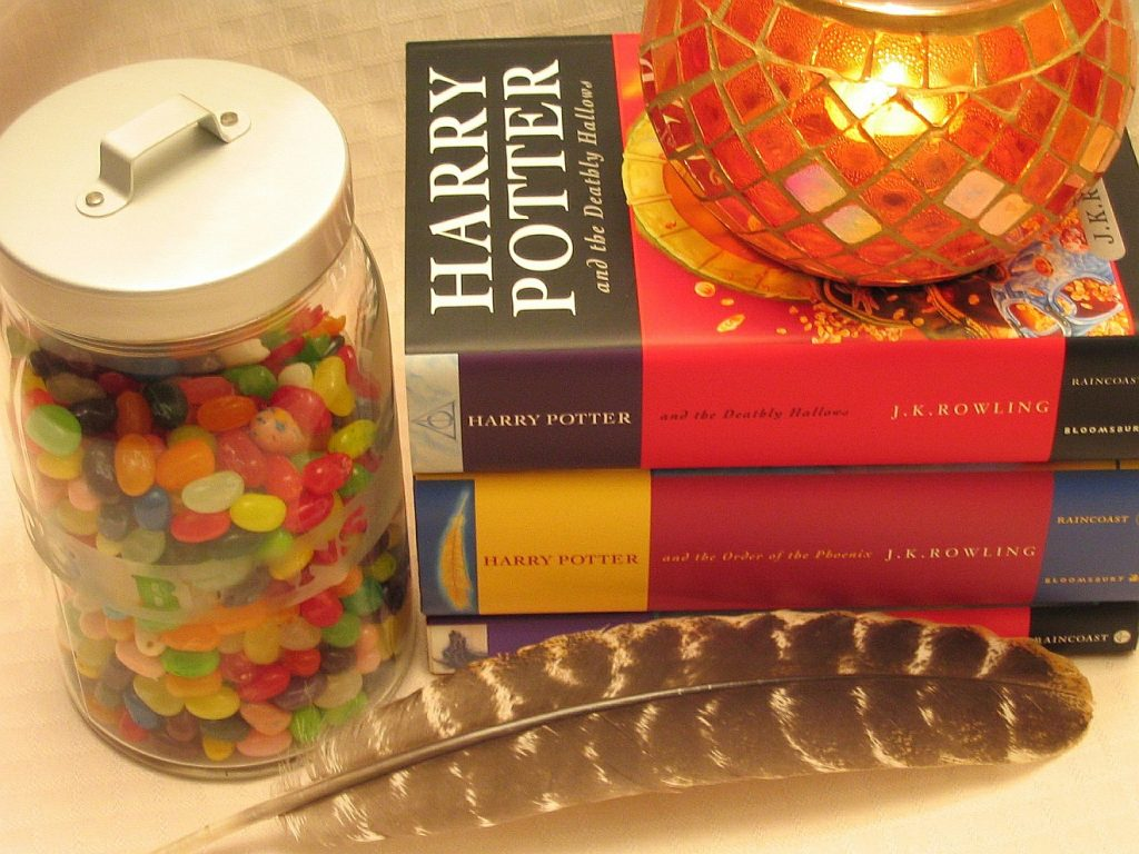 Bücher von Harry Potter neben einer Feder, einer gemütlichen Lampe und einem Glas mit Bonbons entführen aus einer nüchternen Welt