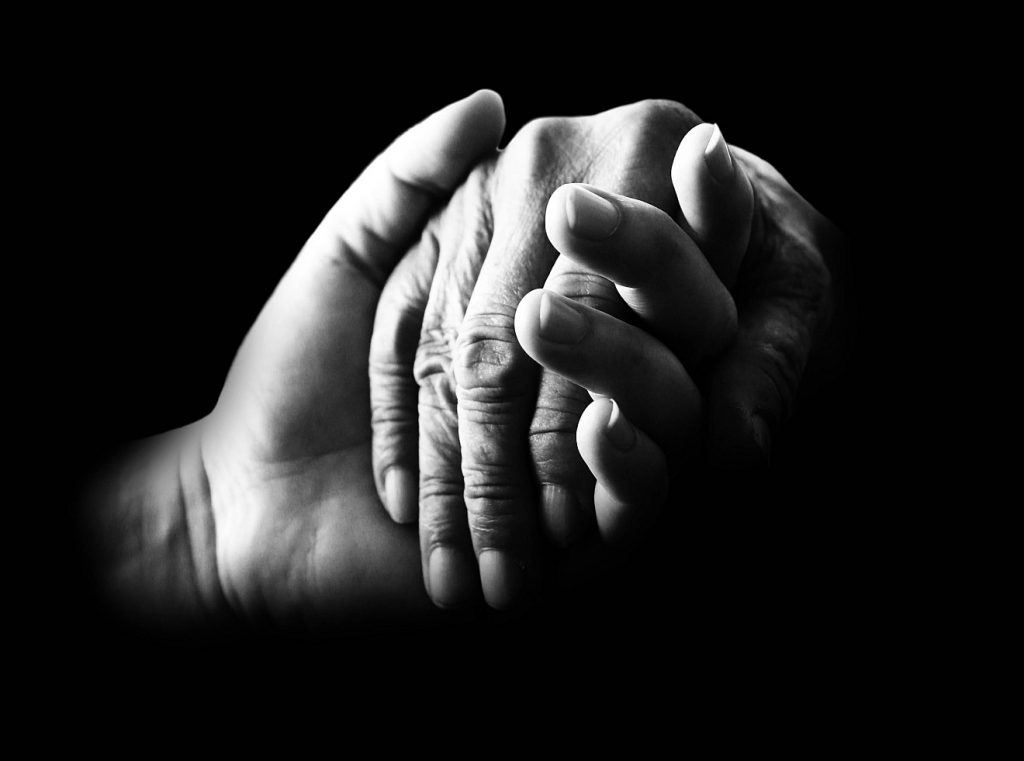 Eine Hand, die eine andere Hand hält, wohl die eines alten Menschen (Schwarzweiß-Foto als Symbol der Barmherzigkeit)