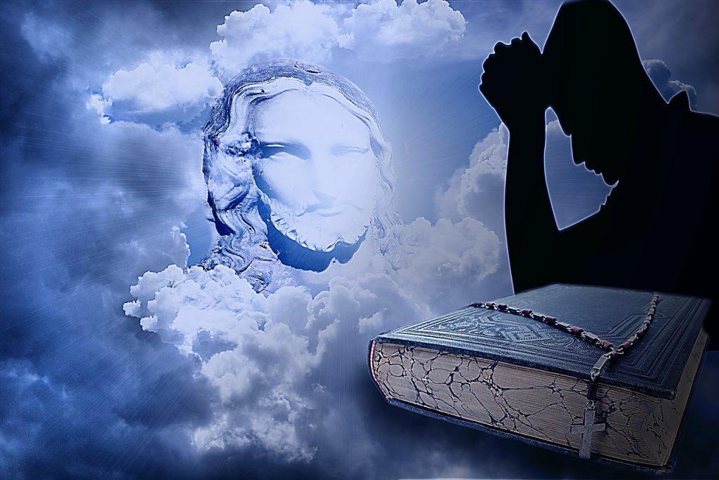 Jesusbild in den Wolken, der Schatten eines betenden Mannes hinter einer Bibel