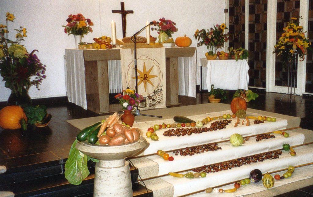 Der geschmückte Altarraum zum Erntedankfest 2001 - mit einem von Kindern mit Obst und Gemüse ausgelegten Umriss eines Apfels auf den Altarstufen - mit Wurm drin!