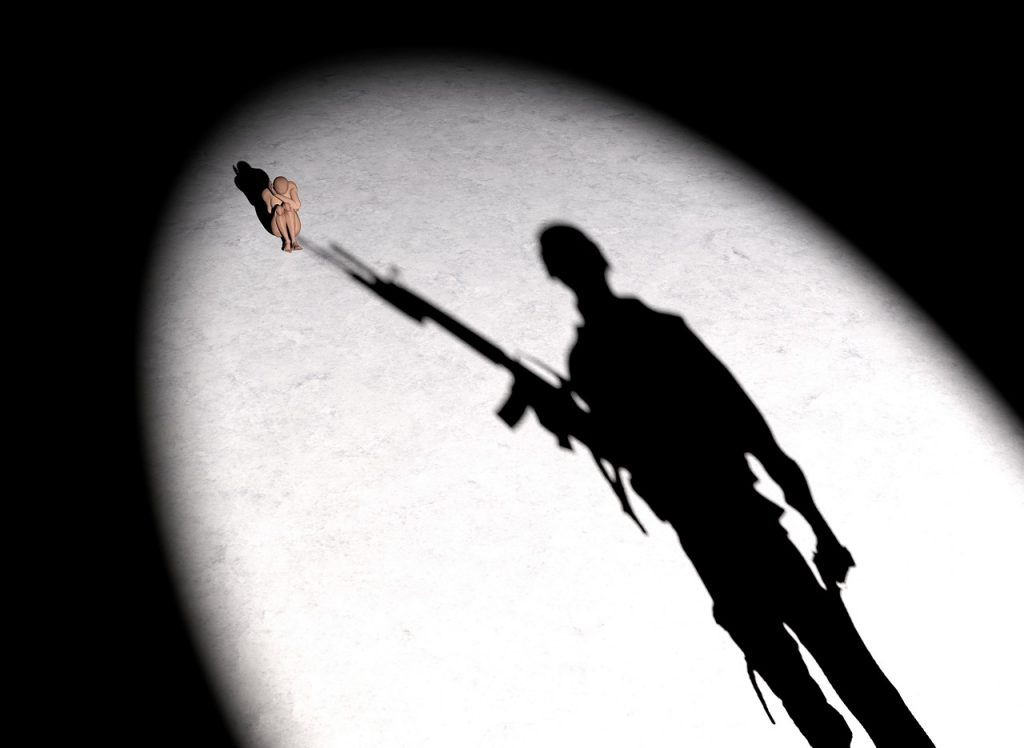 Der Schatten des Gewehrs eines Soldaten zielt auf eine zusammengekauerte kleine Frau