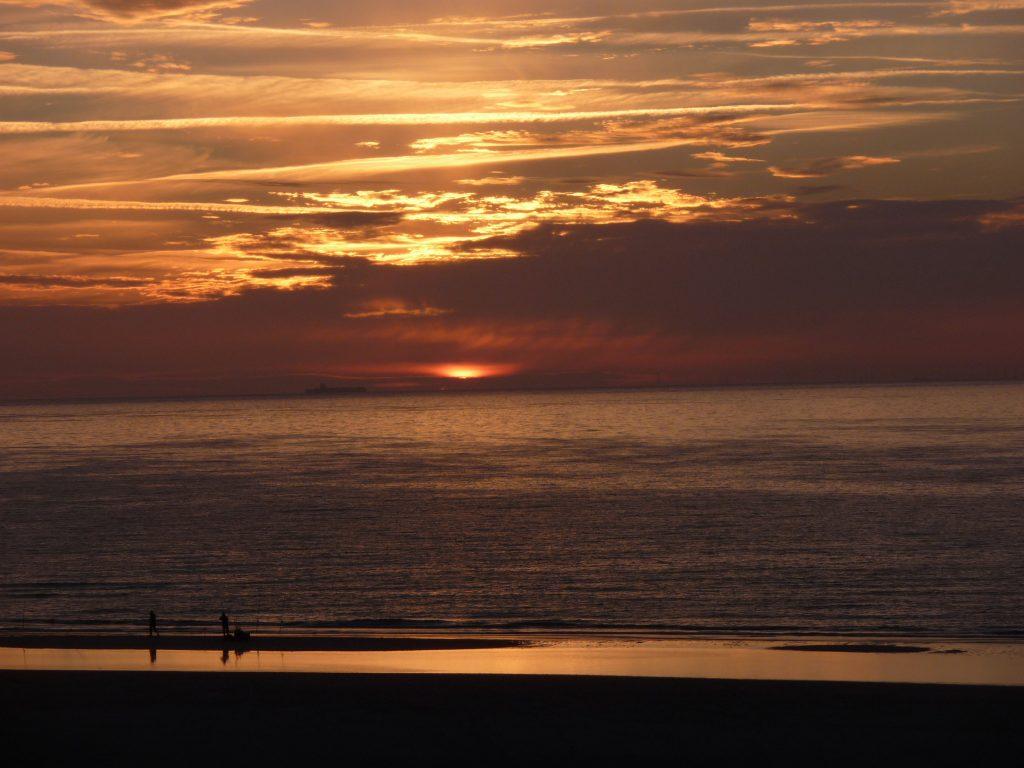 Sonne am Strand knapp über dem Horizont hinter Wolken versteckt