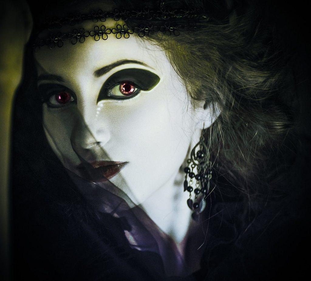 Das Gesicht einer gothic geschminkten und gekleideten geheimnisvollen jungen Frau