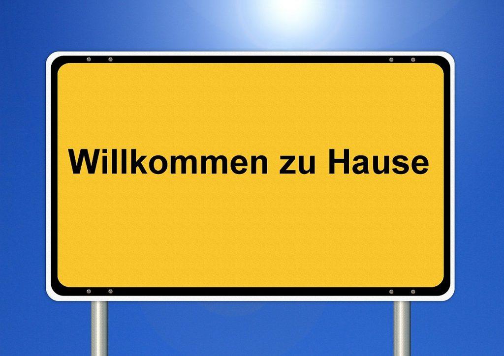 """Ortseingangsschild: """"Willkommen zu Hause"""" vor blauem, sonnigen Himmel"""