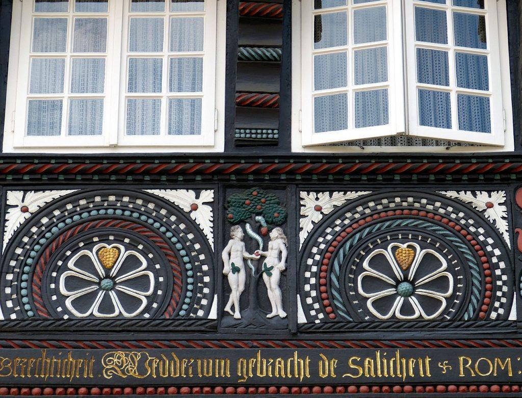 """Adam und Eva vor dem Baum der Erkenntnis an einem Fachwerkhaus mit dem Schriftzug: """"Wedderum gebracht de Salicheit"""""""
